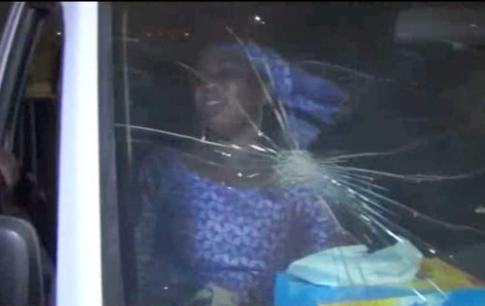 A RESCUED WOMAN SITS IN A VEHICLE WITH BULLET HOLE IN WINDSHIELD NEAR THE SPLENDID HOTEL IN BURKINA FASO.