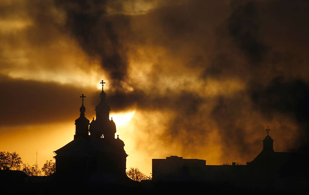 The sun rises above Orthodox Church, left, and Catholic Church in the town of Novogrudok, 150 kilometers ( 93 miles ) west of the capital Minsk, Belarus.
