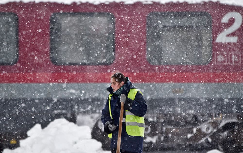 A woman takes a break from clearing snow, back dropped by a delayed train during a blizzard at the Gara de Nord, the main railway station in Bucharest, Romania.