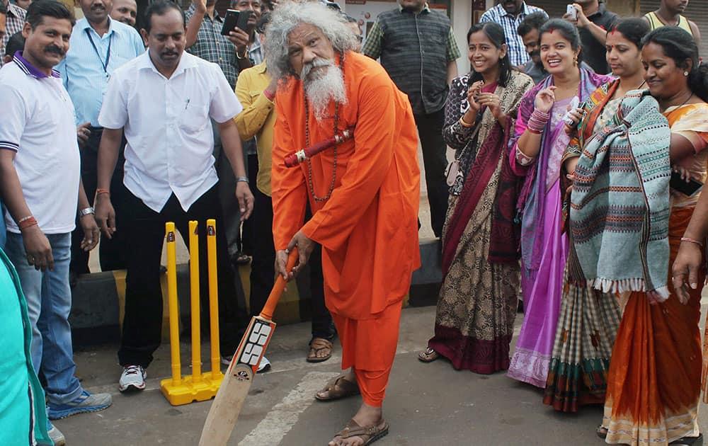 "BJD MP Prashanna Patashani plays cricket during the ""Raahgiri"" day (car-free zone) as others look on, in Bhubaneswa."