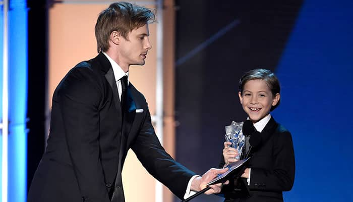 """Bradley James, left, holds the microphone for Jacob Tremblay as he accepts the award for best young actor/actress for """"Room"""" at the 21st annual Critics' Choice Awards at the Barker Hangar."""