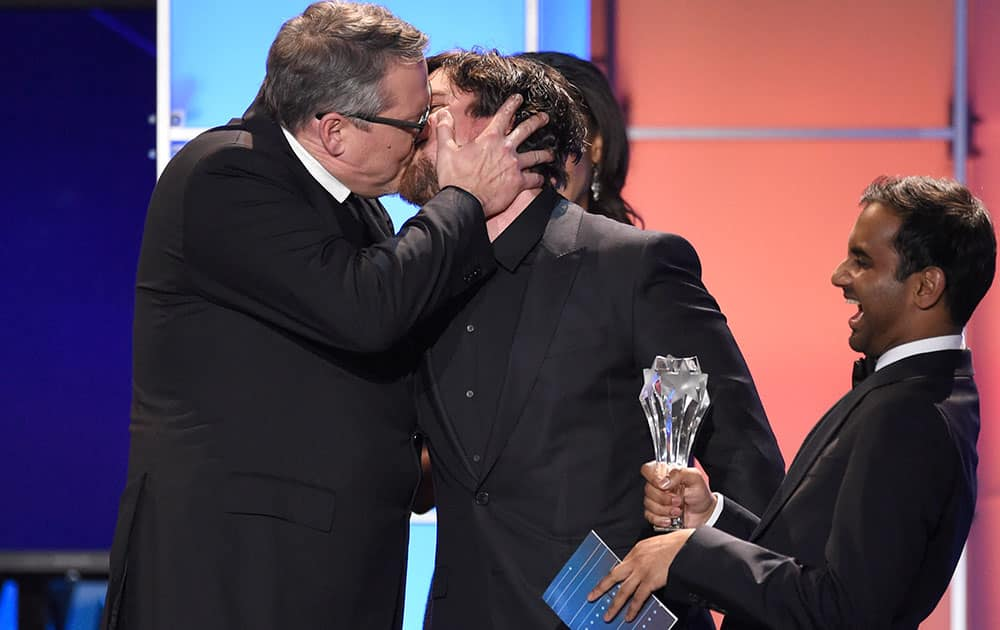 """Adam McKay, left, kisses Christian Bale as he accepts the award for best comedy for """"The Big Short"""" at the 21st annual Critics' Choice Awards."""