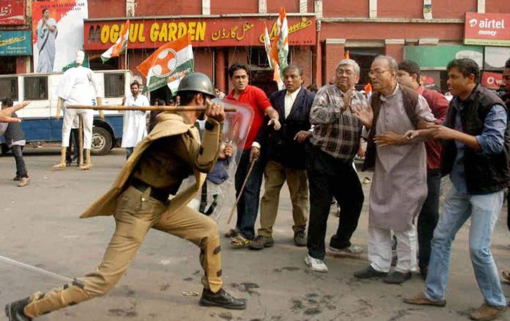 A police man baton charges Congress leader Prakash Upadhyay (2nd right) during an agitation in front of Kolkata.