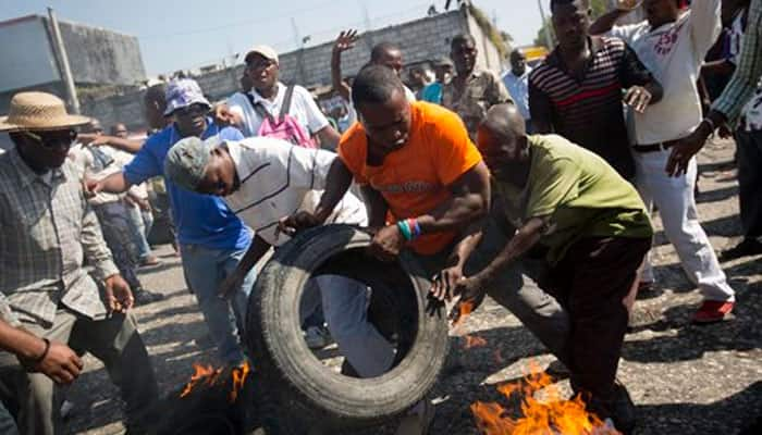 Protesters vow to derail Haiti presidential vote; election offices burned