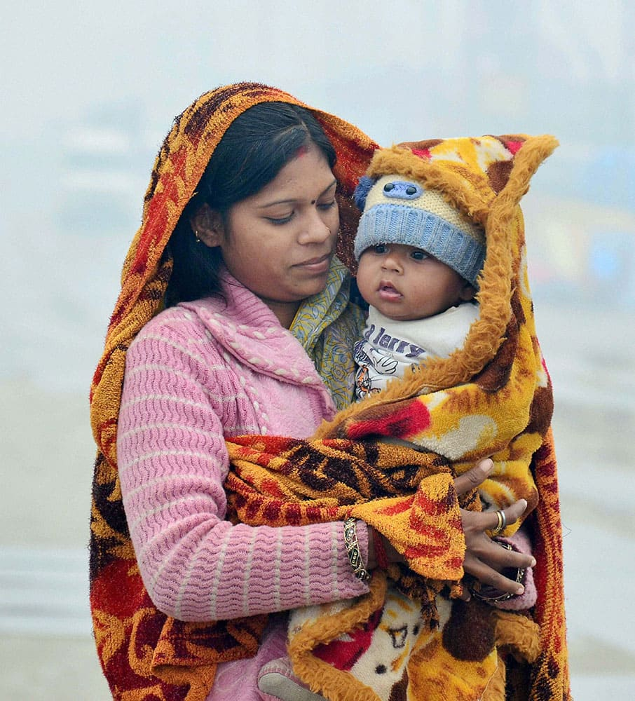 A woman with her child taking protection against cold as mercury dips in Allahabad.