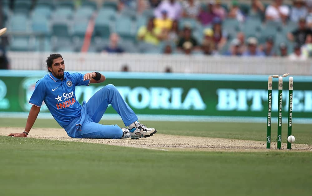 Ishant Sharma sits on the ground after he deflected the ball onto the stumps during their One Day International cricket match against Australia in Canberra, Australia.