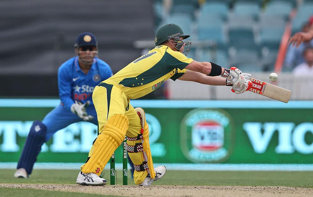 David Warner stretches to play a shot as a wide ball is thrown from Indian bowler Rishi Dhawan during their One Day International cricket match in Canberra, Australia.