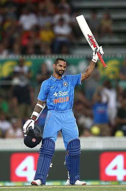 Shikhar Dhawan holds up his bat as he celebrates hitting a century against Australia during their One Day International cricket match in Canberra, Australia.