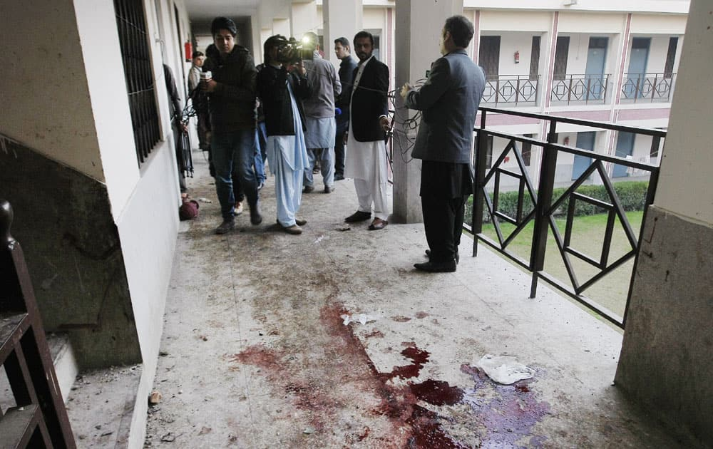 Reporters stand in a corridor at the Bacha Khan University in Charsadda town in Peshawar in Pakistan.