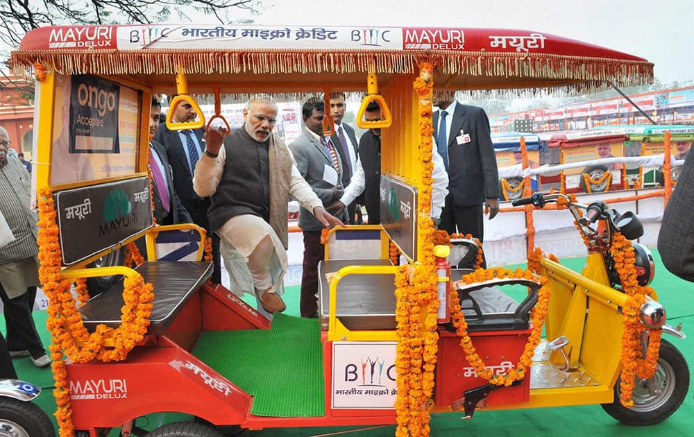 Prime Minister Narendra Modi taking a ride on E-Rickshaw, after the distribution at Rickshaw Sangh programme by the Bhartiya Micro Credit in Lucknow.