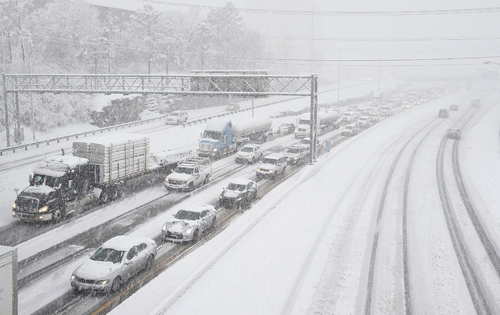 Snow slows down traffic on Interstate 40, in Nashville, Tenn. A blizzard menacing the Eastern United States started dumping snow in Virginia, Tennessee and other parts of the South on Friday as millions of people in the storm's path prepared for icy roads, possible power outages and other treacherous conditions.