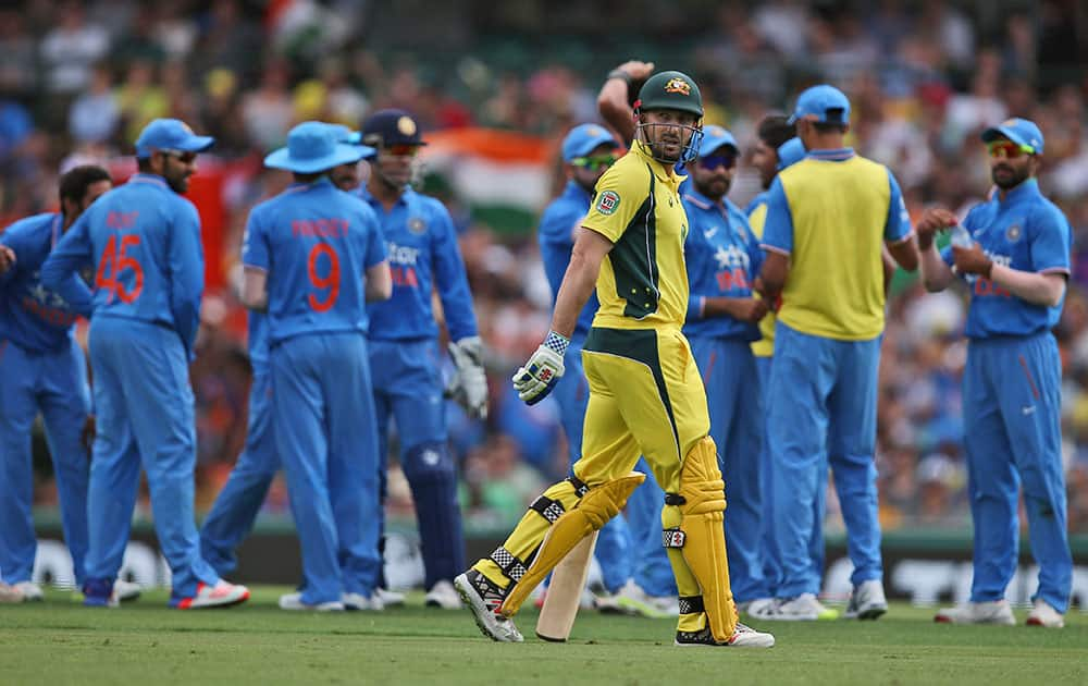 Australia's Shaun Marsh walks past Indian players as they celebrate taking his wicket during their one-day international cricket match in Sydney.