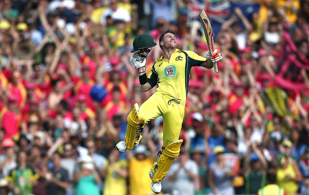 Australia's David Warner leaps into the air as he celebrates after hitting a century against India during their One Day International cricket match in Sydney.