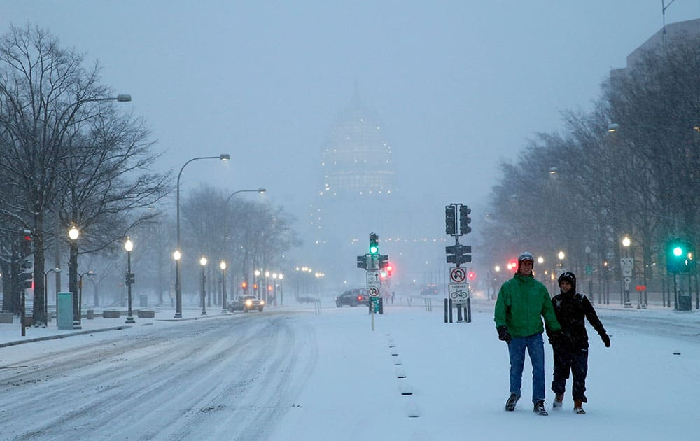 Madison Riley and Katie Lantuh walk down the middle of Pennsylvania Avenue with the US Capitol behind them, as the snow falls, in Washington.