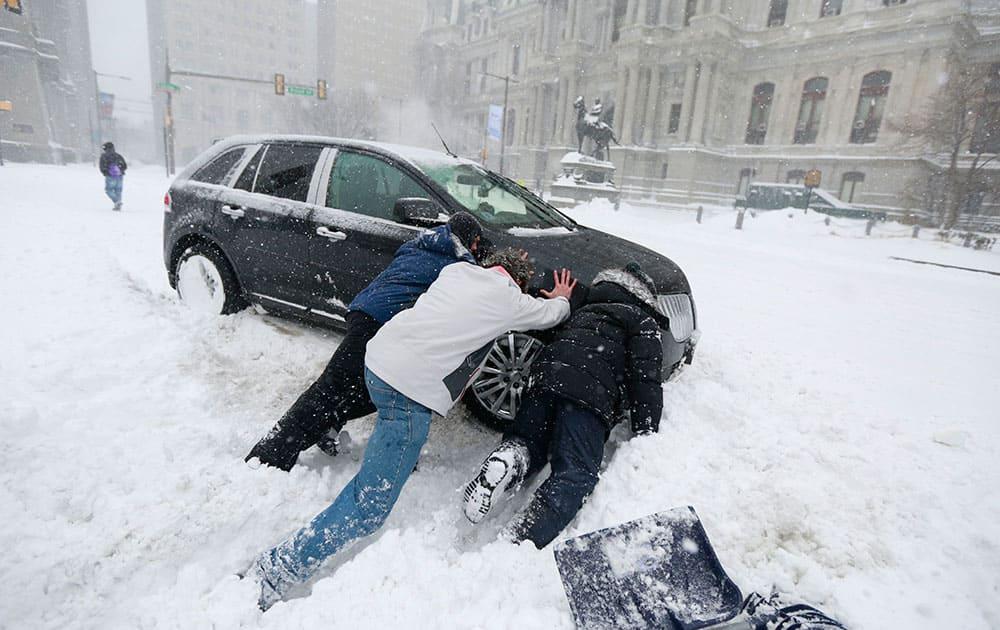 Good Samaritans help a stuck motorist in front of City Hall in Philadelphia as snow falls over the region.