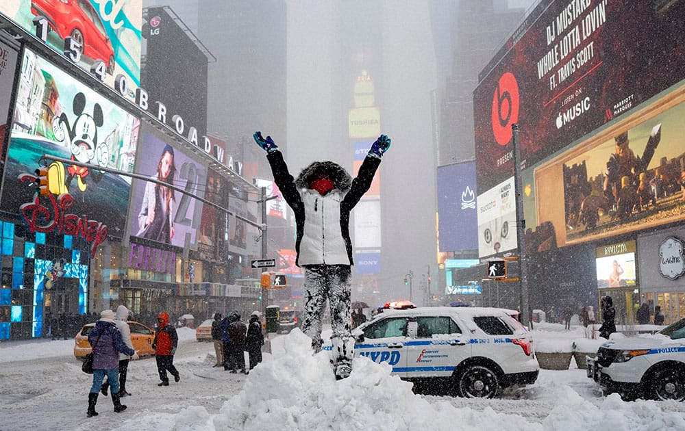Bella Fraker, 10, of Atlanta, stands high on a snow pile as she poses for a family photo in New Yorks Times Square.