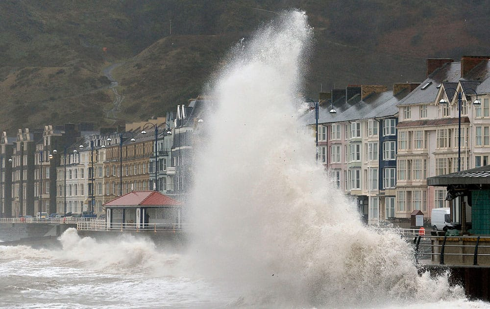 Waves crash against the promenade in Aberystwyth, Wales, as huge swathes of the UK are braced for a deluge of rain.