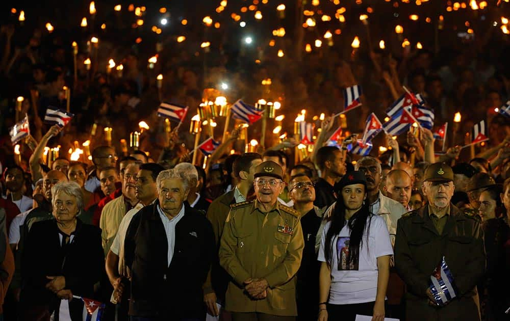 Cuba´s President Raul Castro, center front, along with Uruguays former President Jose Mujica, his wife Sen. Lucia Topolansky, left, President of University Students Federation Jennifer Bello and Revolutionionary Commander Ramiro Valdes, front right, take part in a march with torches in a procession, marking the 163rd anniversary of the birth of Cubas national independence hero Jose Marti, in Havana, Cuba.