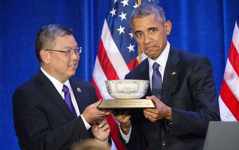 President Barack Obama, is presented a commemorative bowl by Rep. Mark Takai, D- Hawaii, left, before speaking at the House Democratic Issues Conference in Baltimore, Md.