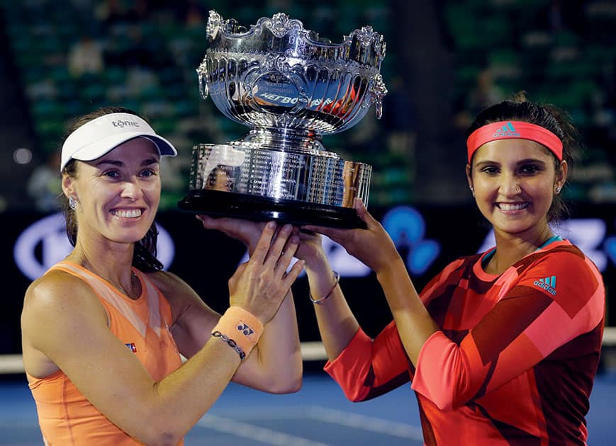Martina Hingis of Switzerland and Sania Mirza of India hold their trophy aloft after defeating Czech Republic's Andrea Hlavackova and Lucie Hradecka in the women's doubles final at the Australian Open tennis championships in Melbourne, Australia.