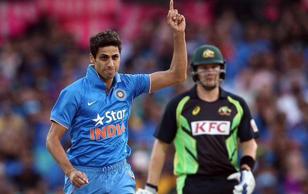 Indian bowler Ashish Nehra points up to the air as he celebrates taking the wicket of Australia's Usman Khawaja during their T20 International cricket match in Sydney, Australia.