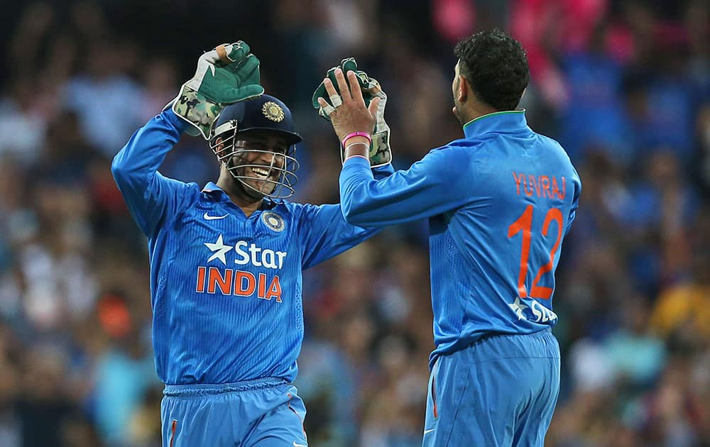 Indian bowler Yuvraj Singh, right, celebrates with MS Dhoni after taking the wicket of Australia's Glenn Maxwell during their T20 International cricket match in Sydney, Australia.