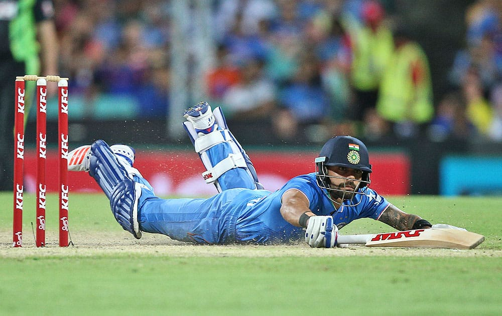 India's Virat Kohli dives into his crease after taking a quick single during their T20 International cricket match against Australia in Sydney, Australia.