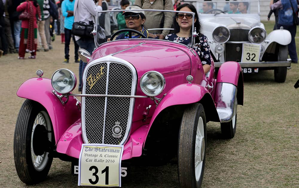 A woman drives a 1933 Fiat car during the Statesman vintage & classic car rally in Kolkata.