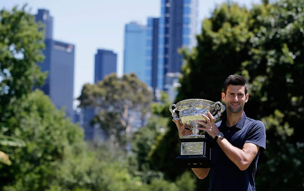 Serbia's Novak Djokovic poses for photos with his Australian Open trophy at Government House in Melbourne, Australia.