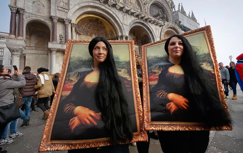 Two carnival revellers masquerade as Leonardo da Vinci's painting 'Mona Lisa' pose in St. Mark's Square in Venice, Italy.