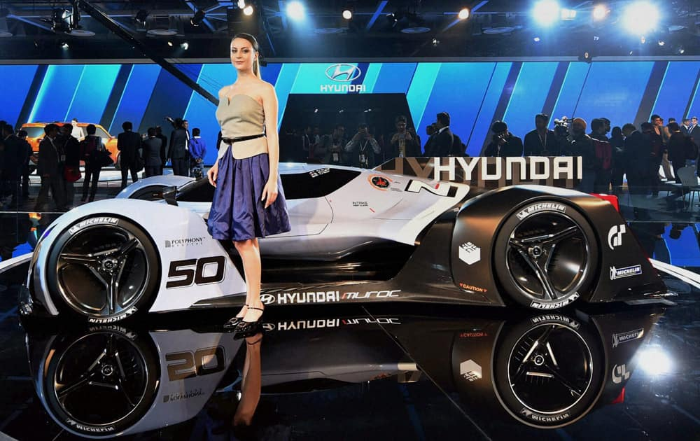 A model poses in front of a sports car displayed at the Hyundai stall at Auto Expo 2016 in Greater Noida.