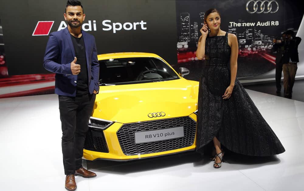 Indian cricketer Virat Kohli and Bollywood actor Alia Bhatt, right pose during the launch of Audi R8 V10 plus at the Auto Expo in Greater Noida, near New Delhi, India, Wednesday, Feb. 3, 2016.