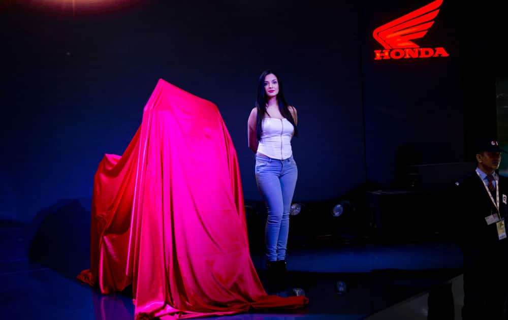 An Indian model stands next to soon to be launched Honda motorcycle at the Auto Expo in Greater Noida, near New Delhi, India , Wednesday, Feb. 3, 2016.