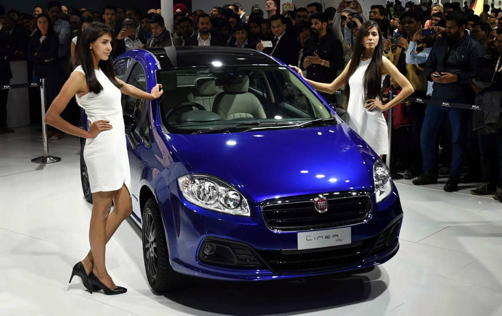 Models pose with Fiat Motors Linea at Auto Expo 2016 in Greater Noida on Thursday.