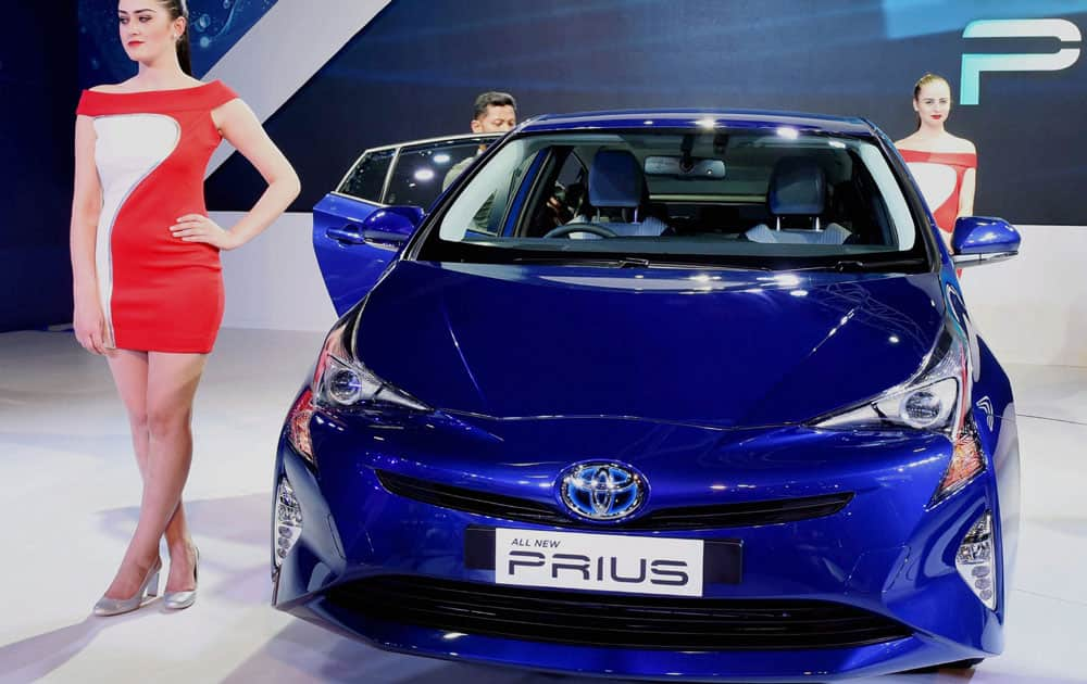 A model poses next to Toyota's 4th generation Prius, Hybrid car at the Auto Expo in Greater Noida.