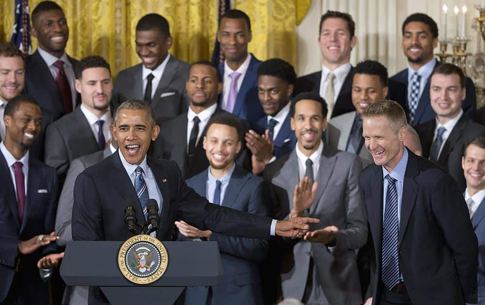 President Barack Obama points to Golden State Warriors head basketball coach Steve Kerr, right, during a ceremony in the East Room of the White House in Washington.