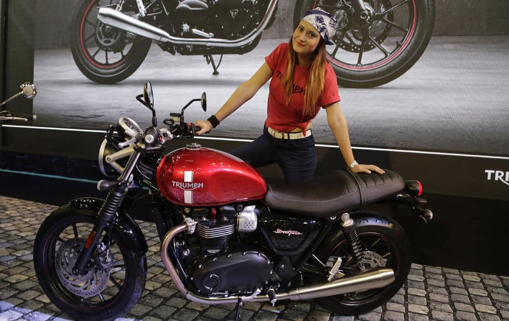 A model poses with Triumph's 900cc Street Twin motorcycle at the Auto Expo in Greater Noida, near New Delhi.