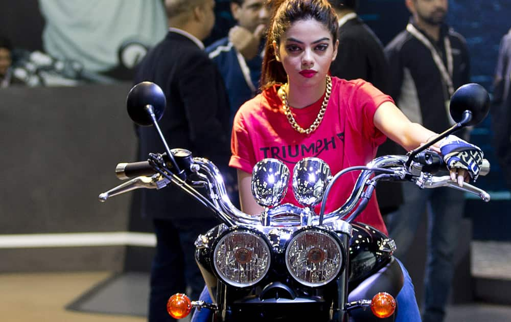 An Indian model sits on a Triumph motorcycle during the Auto Expo, in Greater Noida, near New Delhi.