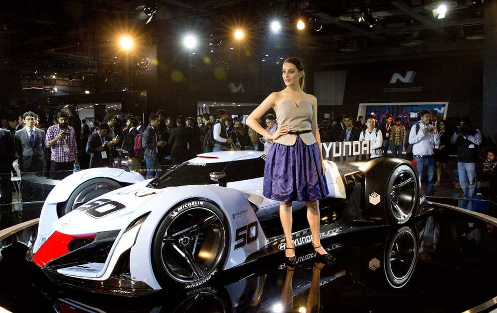 An Indian model stands next to Hyundai 2025 vision Grati Turismo at the Auto Expo in Greater Noida, near New Delhi.