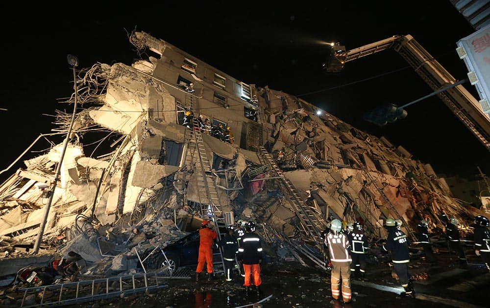 Rescue workers search a toppled building after an earthquake in Tainan, Taiwan.