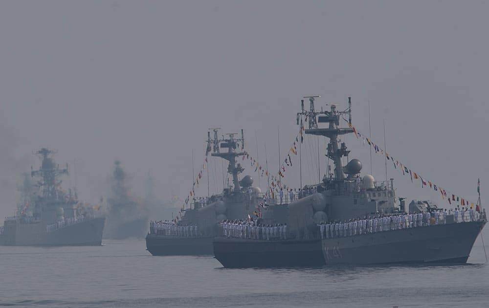 Indian sailors on a veer class corvette take their caps in their hand as they salute the Indian President Pranab Mukherjee, during the International Fleet Review in Vishakapatnam.