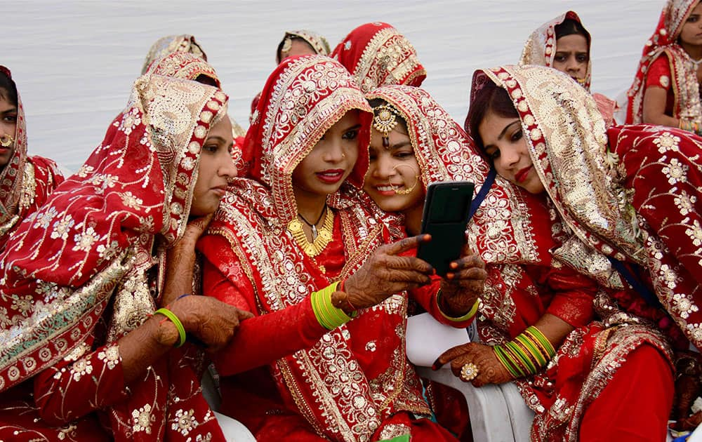 Brides taking selfie during mass marriage event in Ahmadabad.