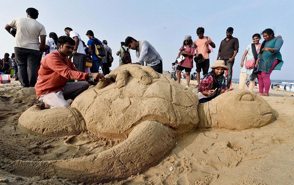 College students and volunteers make sand sculpture of turtles at Marina Beach as part of a Save a Turtle campaign at marina beach in Chennai.