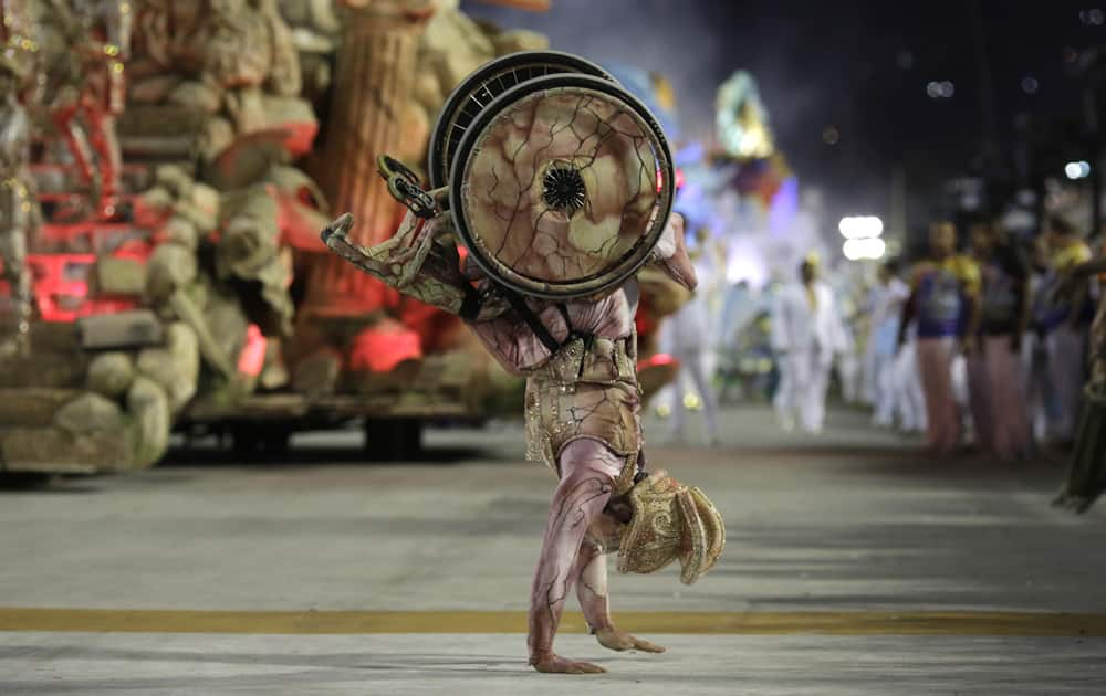 A performer on a wheelchair from Uniao da Ilha samba school, walks on his hands during the Carnival celebrations at the Sambadrome in Rio de Janeiro, Brazil.