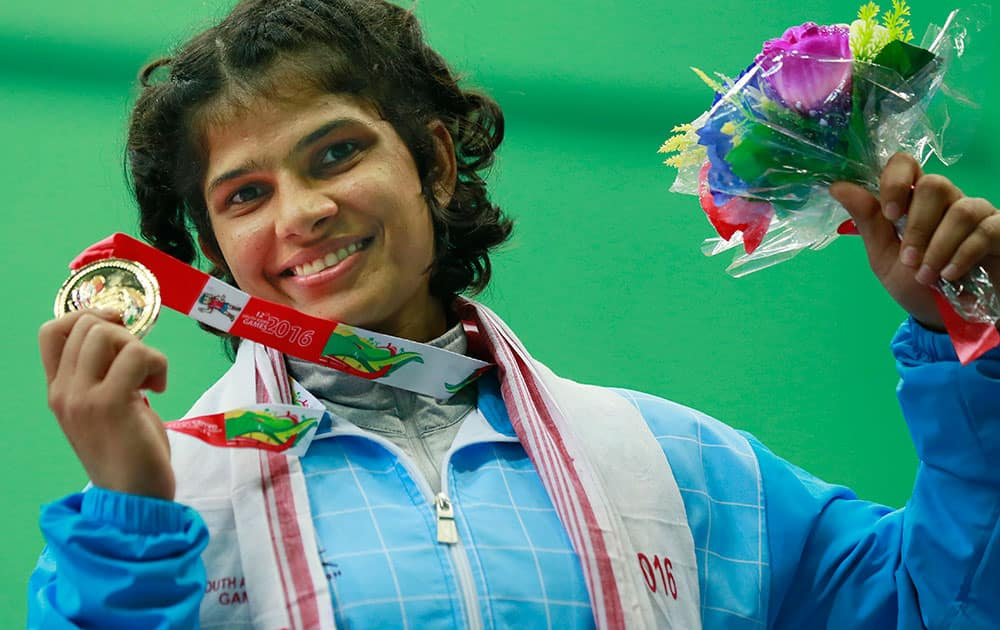 India's Shilpi Sheoran displays the gold medal during the 63 kg women wrestling medal ceremony in the South Asian Games in Gauhati, India.
