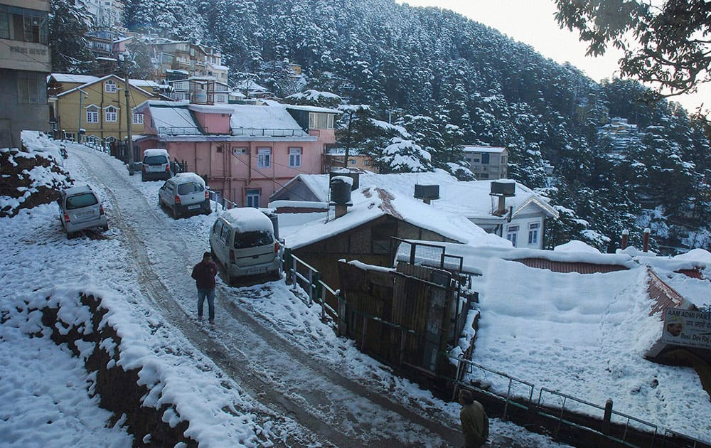 A man walks on snow covered road after heavy snowfall in Shimla.