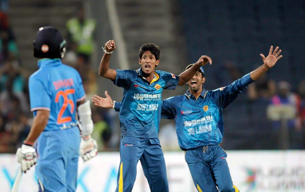 Sri Lanka cricket player Kasun Rajita, centre, celebrates after taking Indian player Ajinkya Rahane's wicket during first T20 match between India and Sri Lanka in Pune.