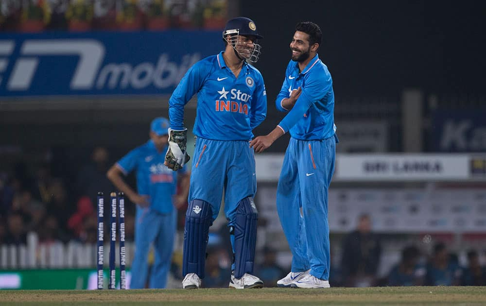 Cricketers Mahendra Singh Dhoni and Ravindra Jadeja share a light moment as they wait for a third umpire's decision against Sri Lanka during the second T20 match of a three match series between the two countries, in Ranchi.