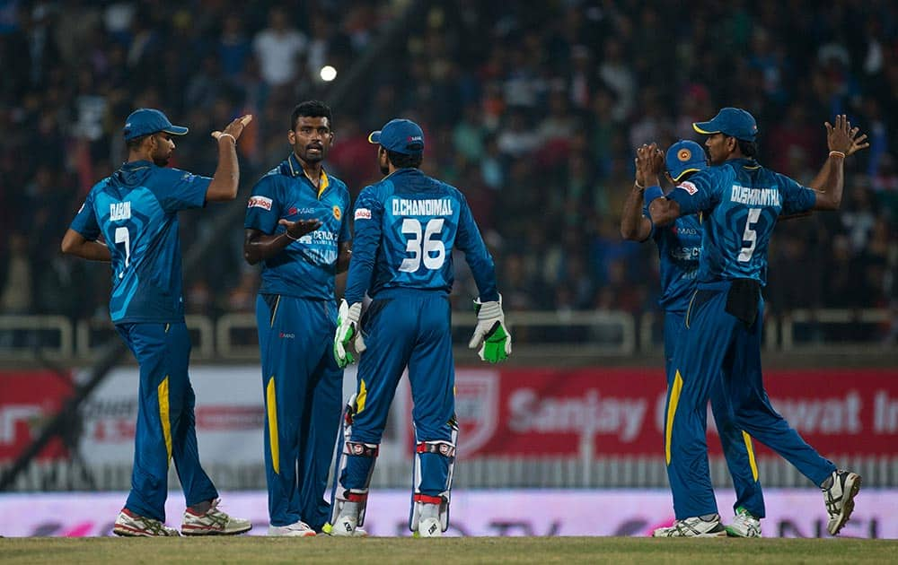 Sri Lankan bowler Thisara Perera, second left, who claimed a hat-trick against India, celebrates with teammates after claiming an Indian wicket during the second T20 match of a three match series between the two countries, in Ranchi.