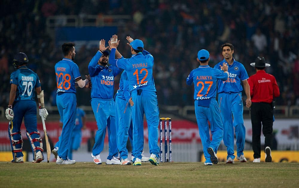 Cricketers celebrate the fall of Sri Lankan batsman Seekkuge Prasanna during the second T20 match of a three match series between the two countries, in Ranchi.
